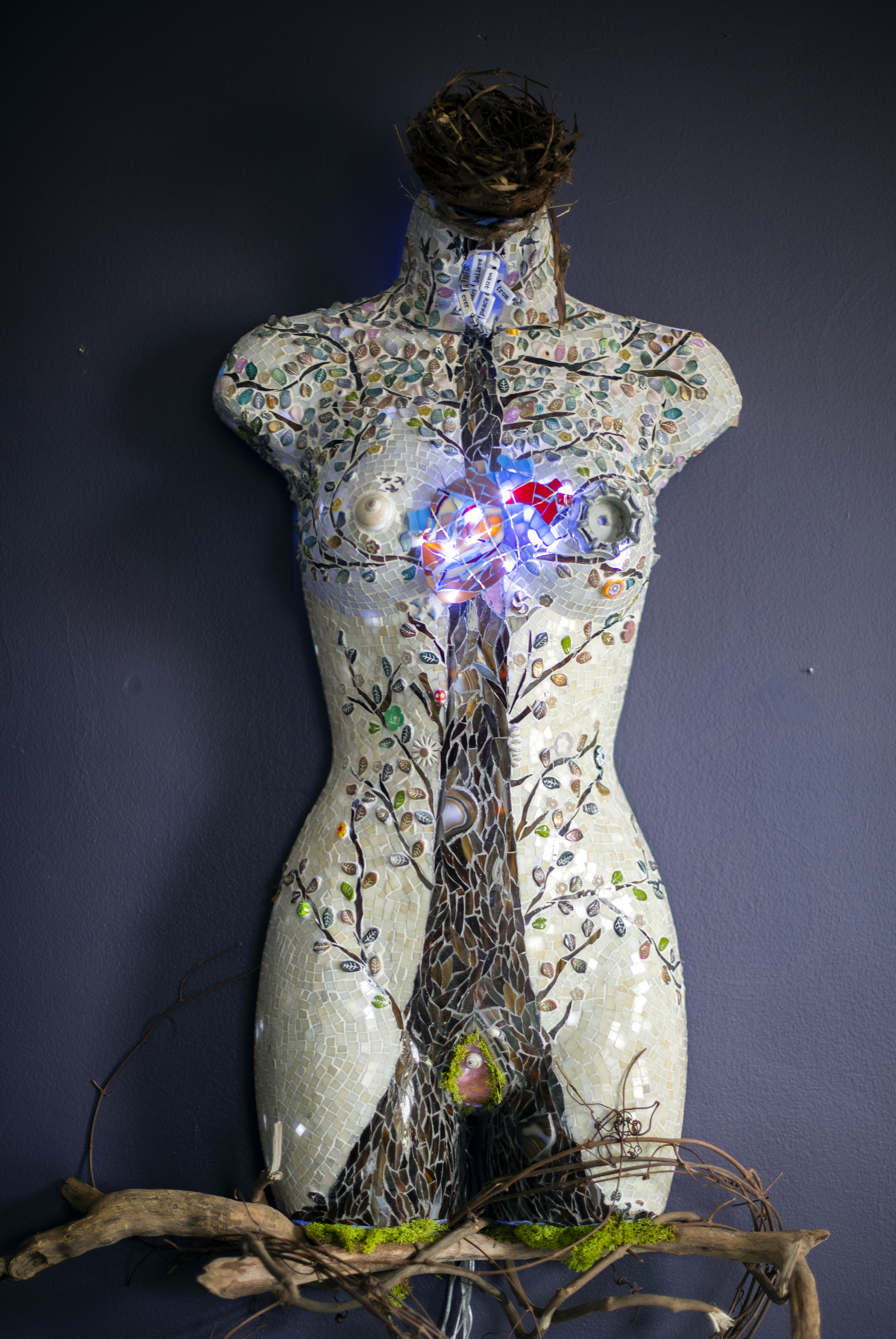 mannequin torso form covered with glass mosaic of tree and heart