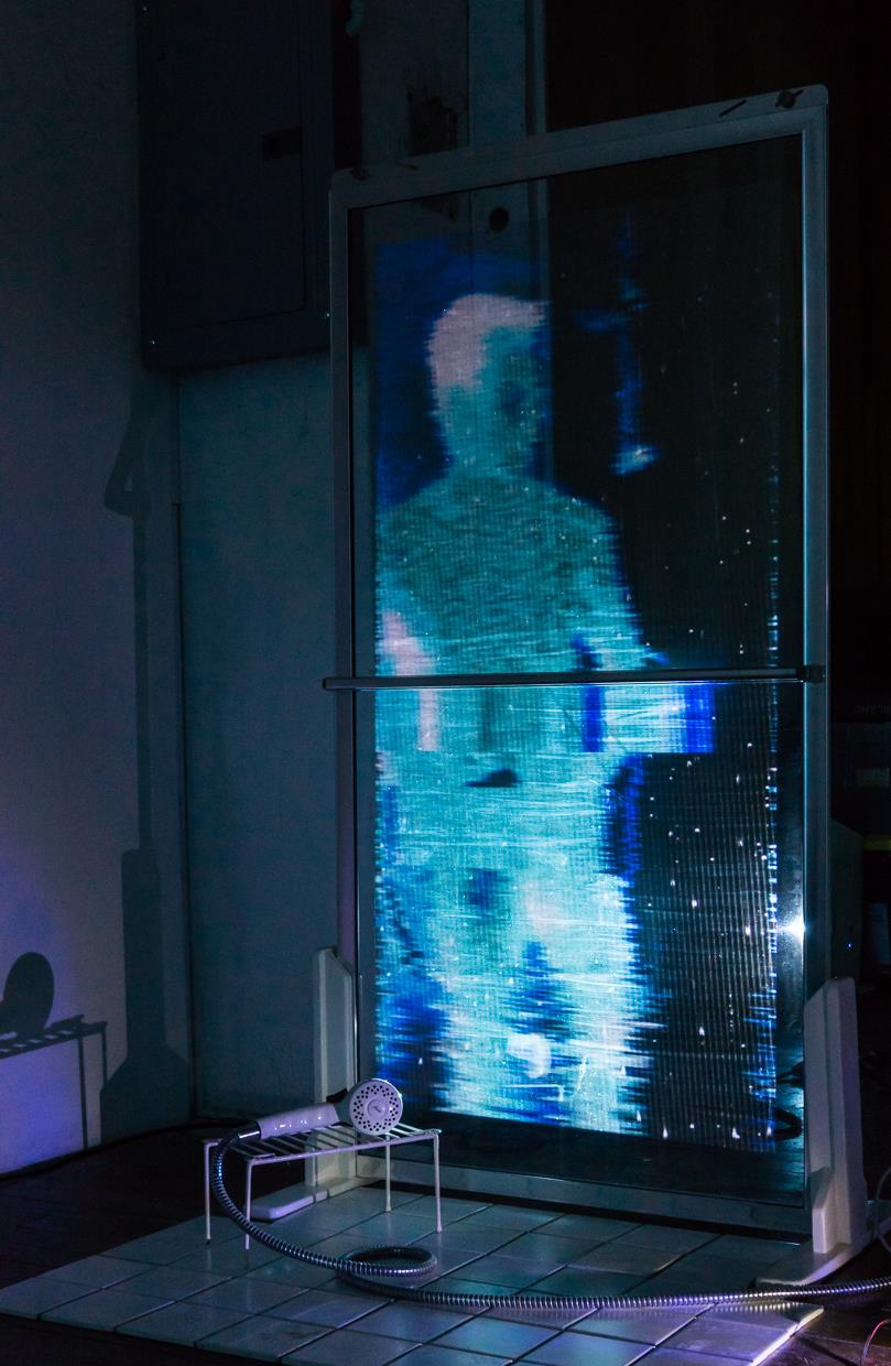 Digitally mangled video of showering individuals is projected on glass shower door coated in 'holographic' projection film. Show