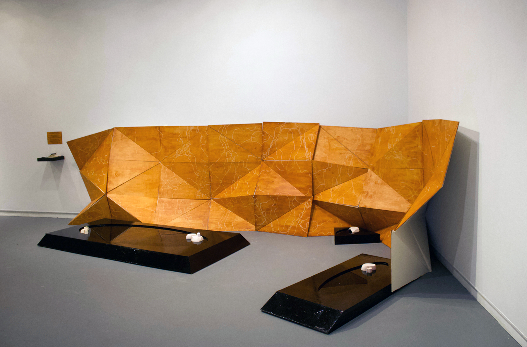 Kinetic wooden structure, comprised of triangle pieces and backed with canvas. On the floor are three black reflecting pools.