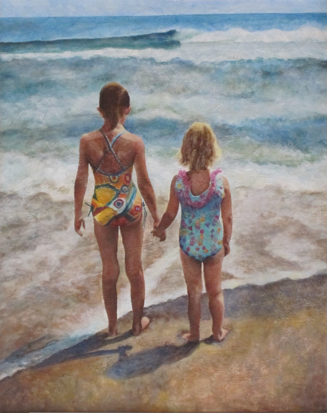 Two young girls holding hands watching the ocean.