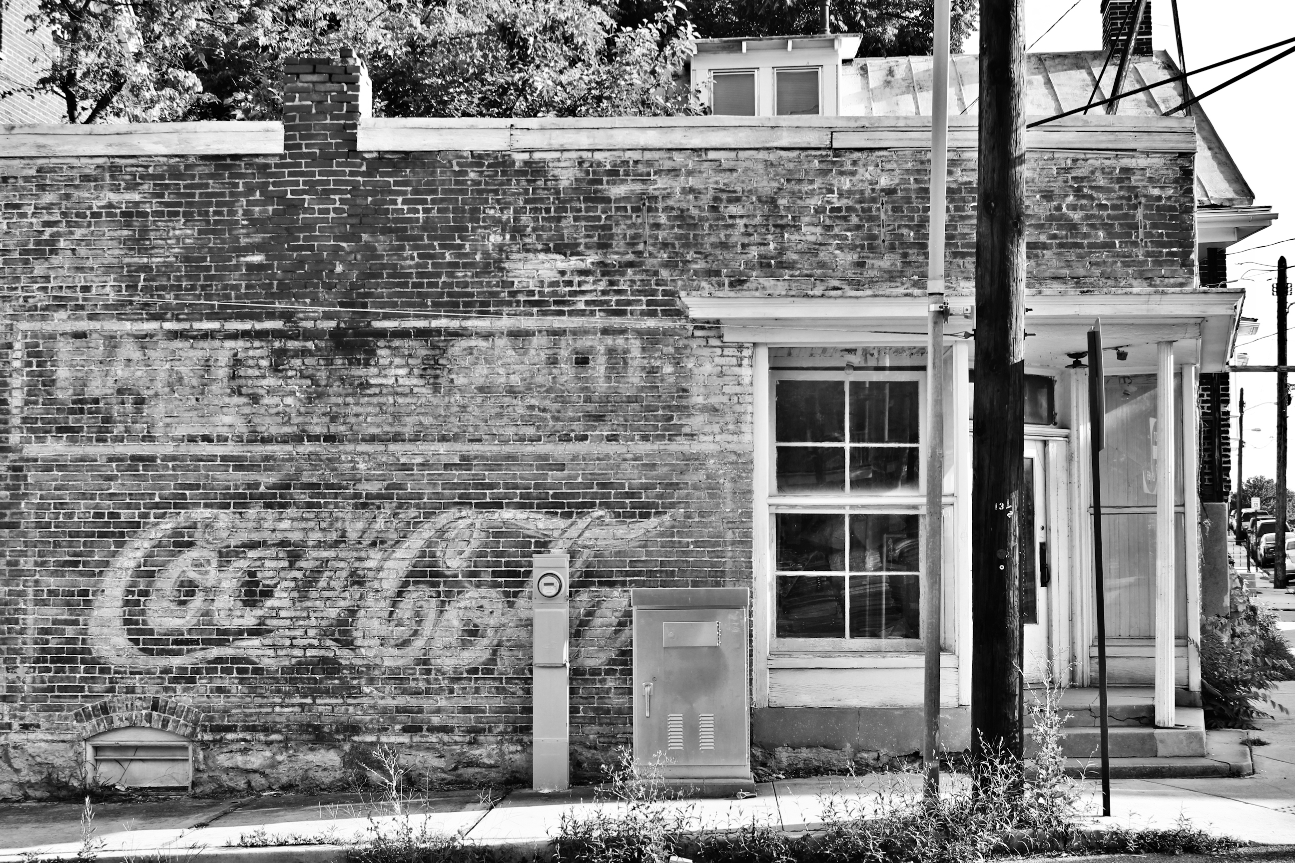 Faded vintage Coca Cola logo on the side of a closed down brick corner store.