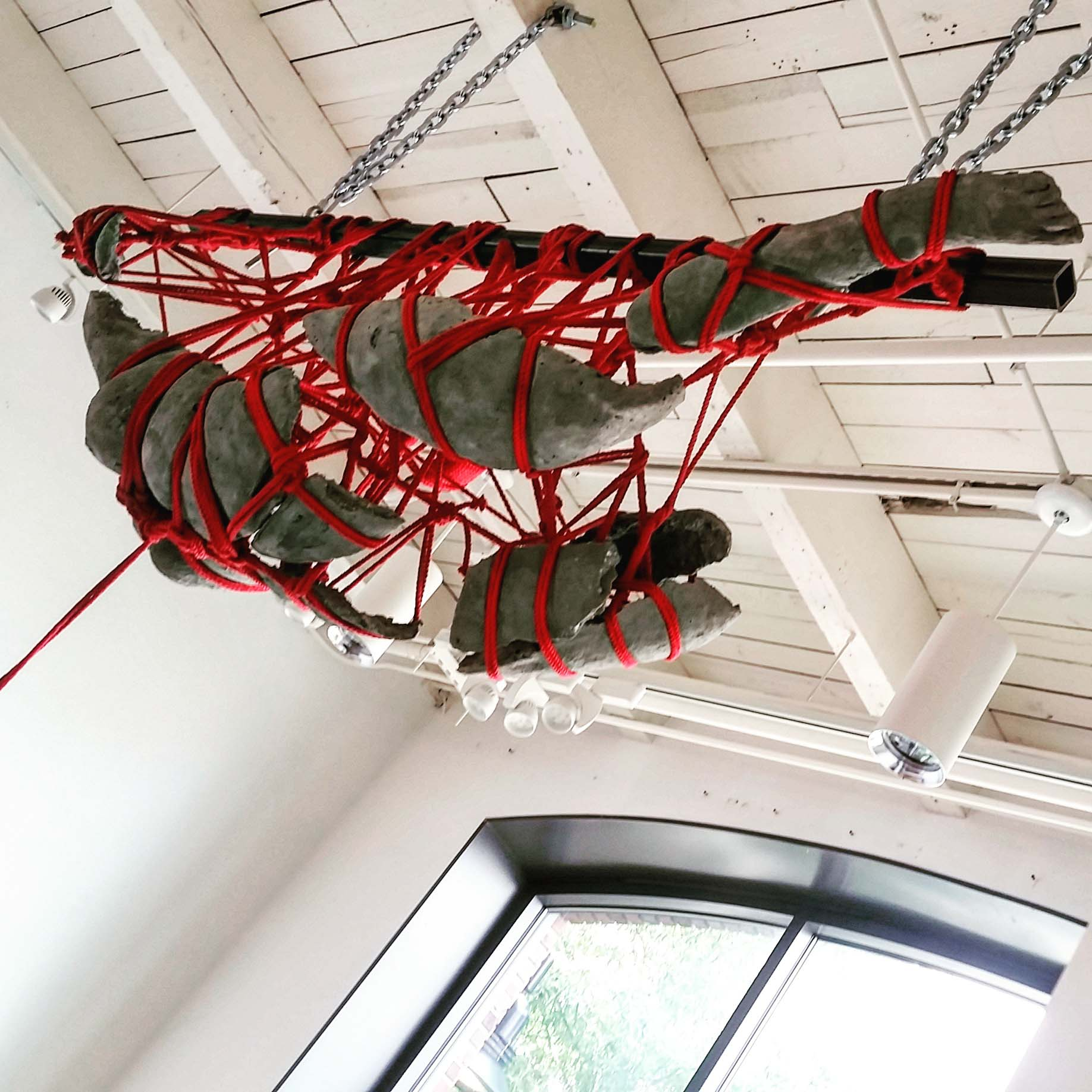 Female form, full body cast, suspended 25ft in the air in a kinbaku rope style with red rope.
