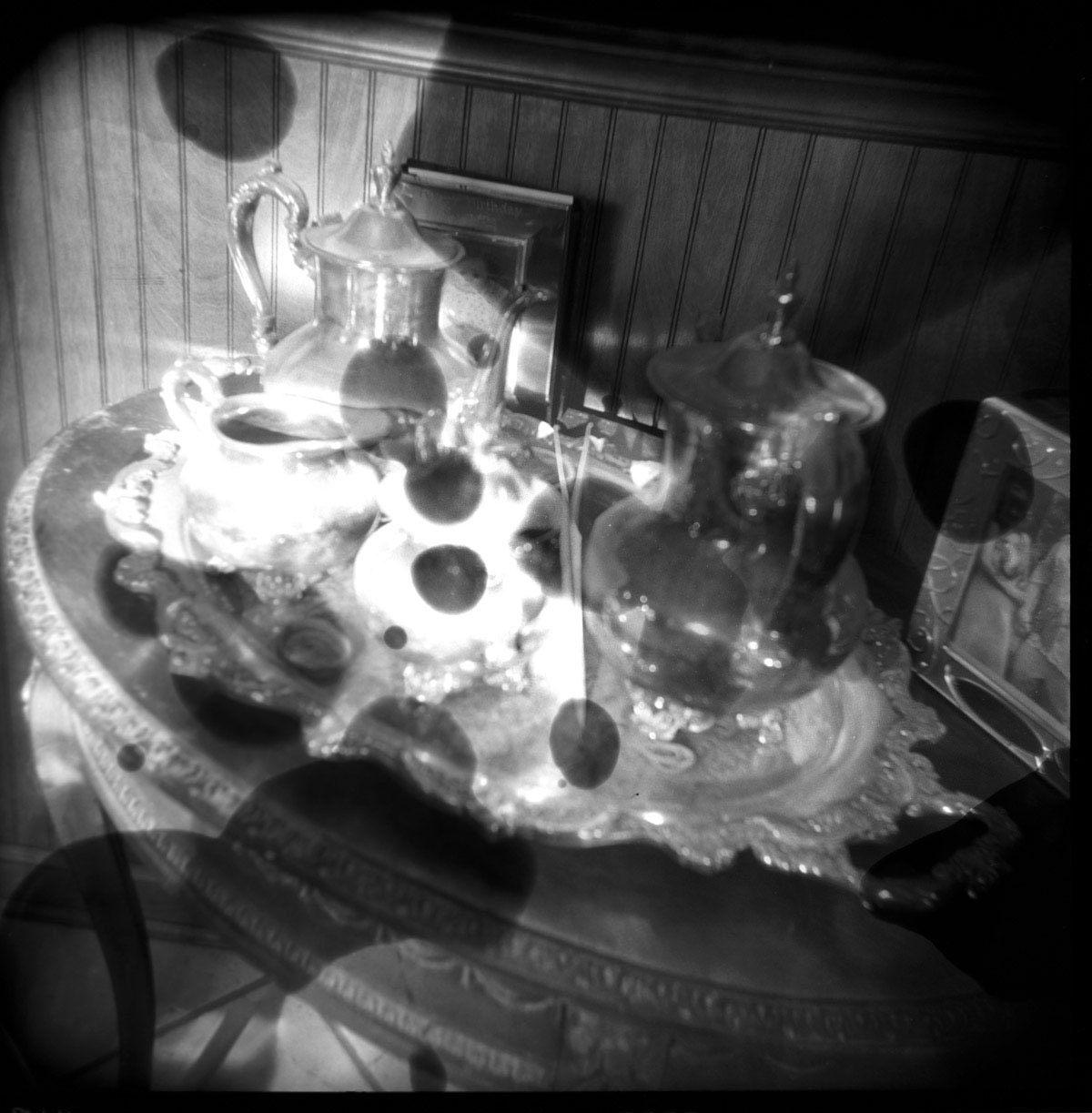 chemically altered silver gelatin print of a sterling silver tea set