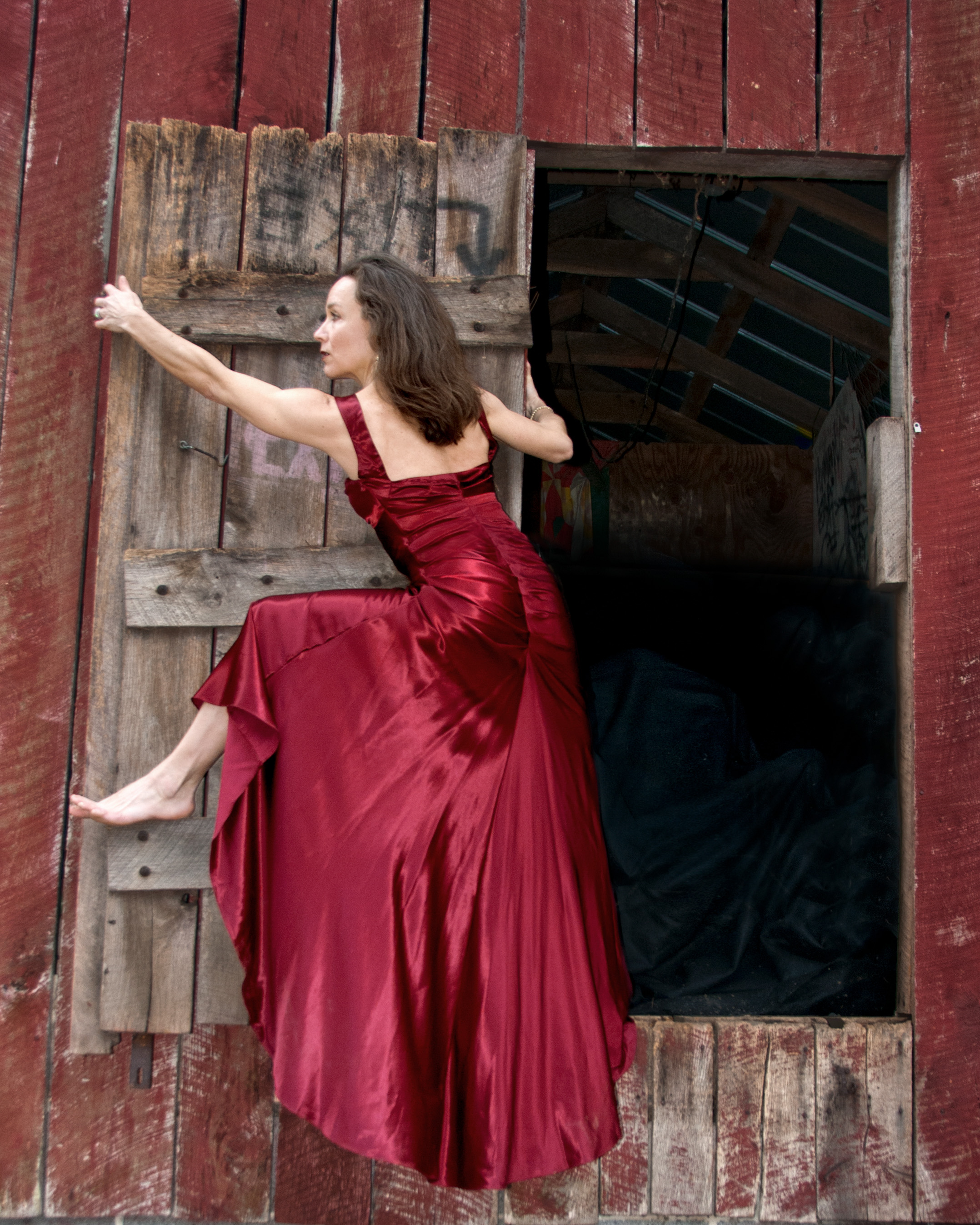 Strong woman in red gown exits barn hanging on rustic door.