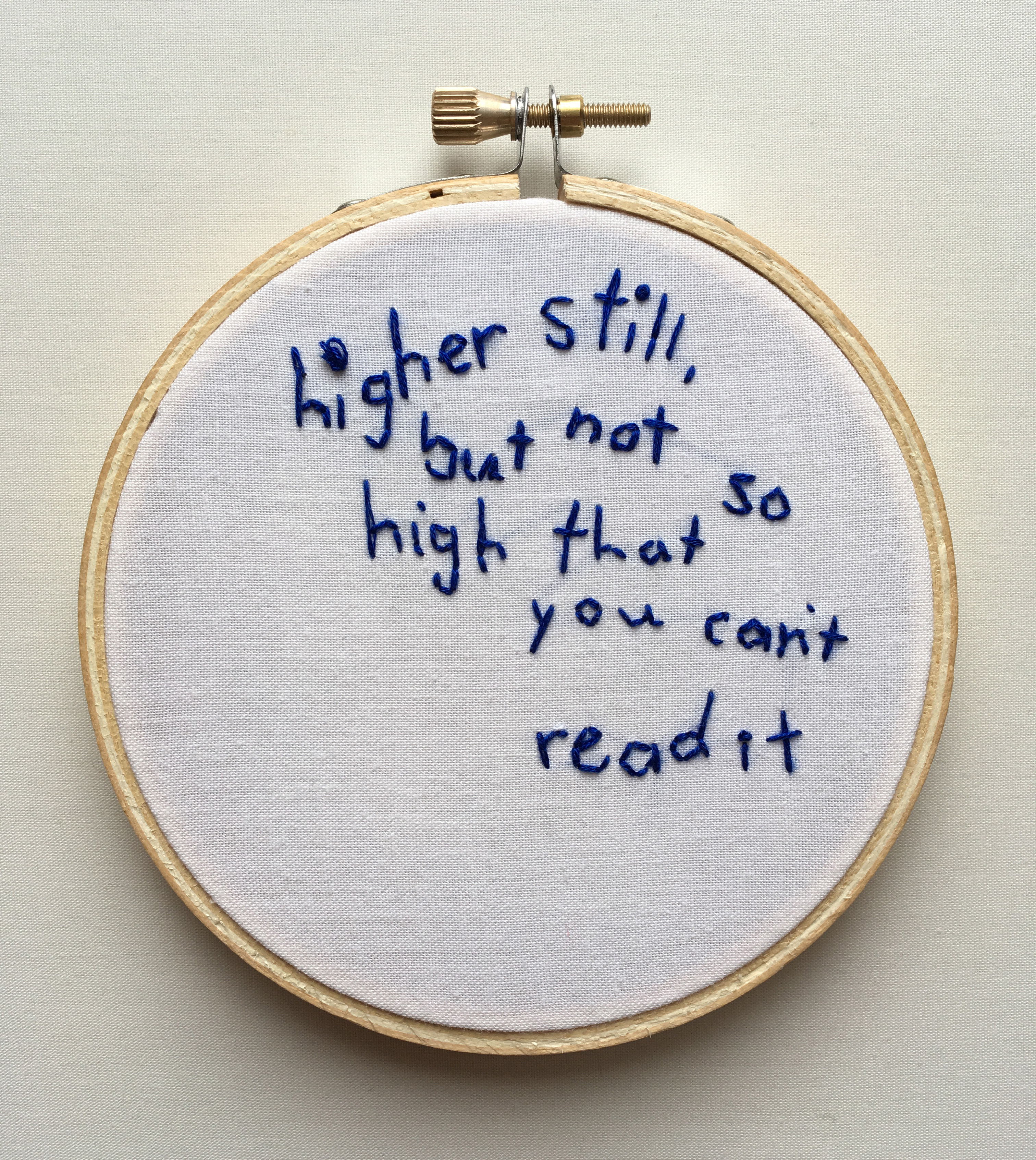 "An embroidery of the text ""higher still, but not so high that you cant read it"" on white fabric stretched over a hoop."