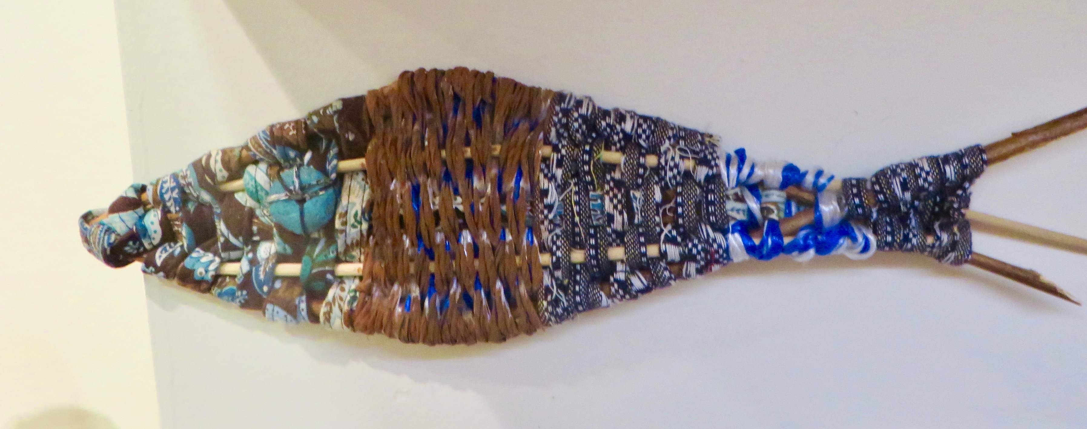 Woven fish sculpture with glass eye and reed body.