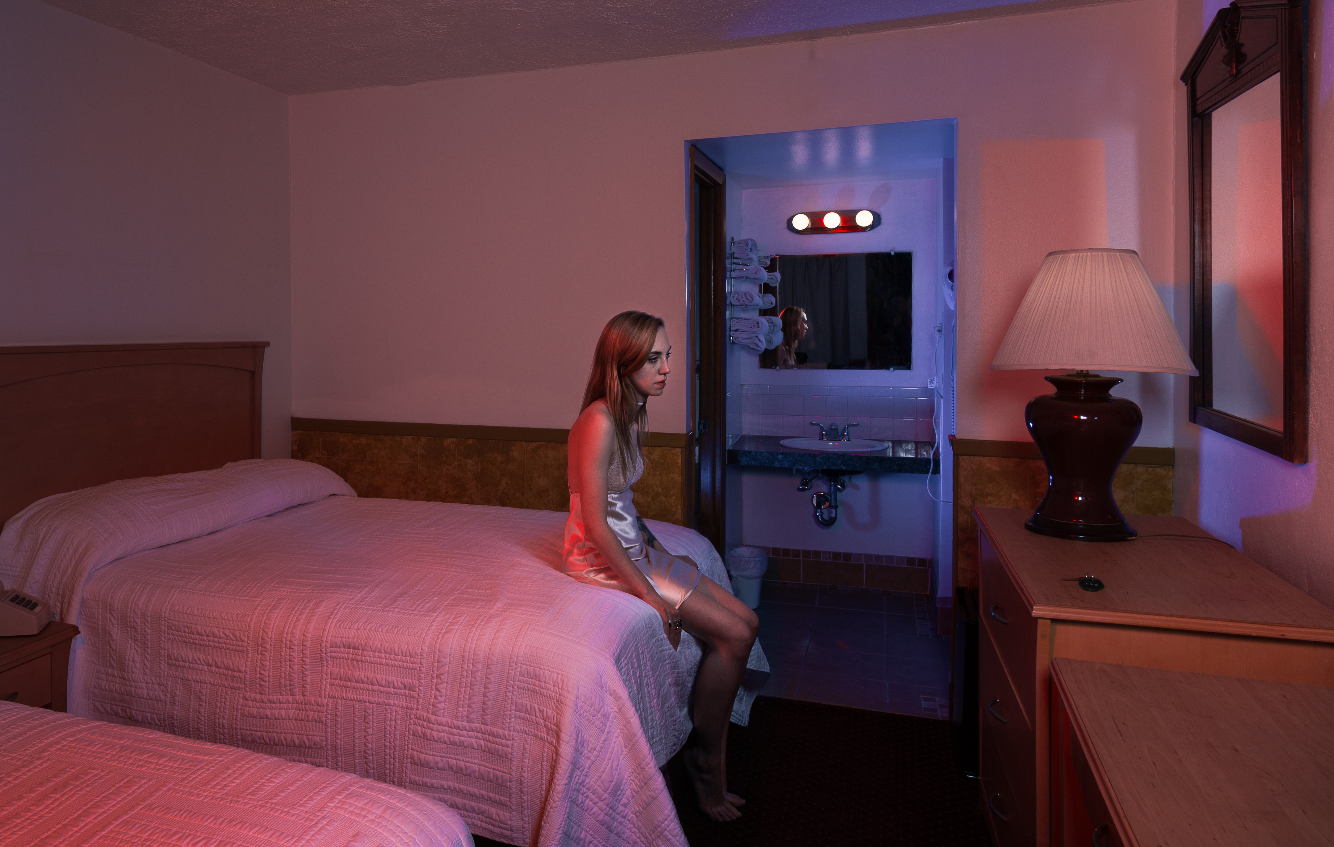 Photograph of female sitting on the edge of a bed in a motel room