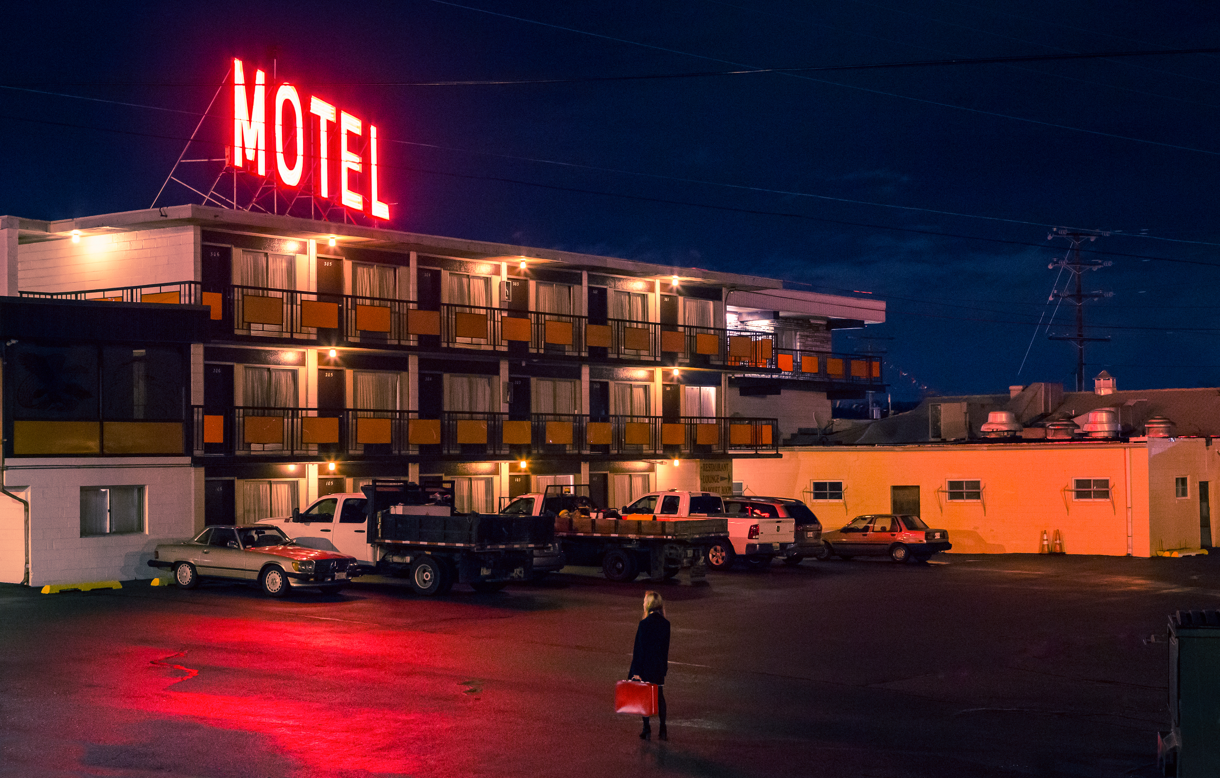 Woman standing with a suitcase looking at a motel