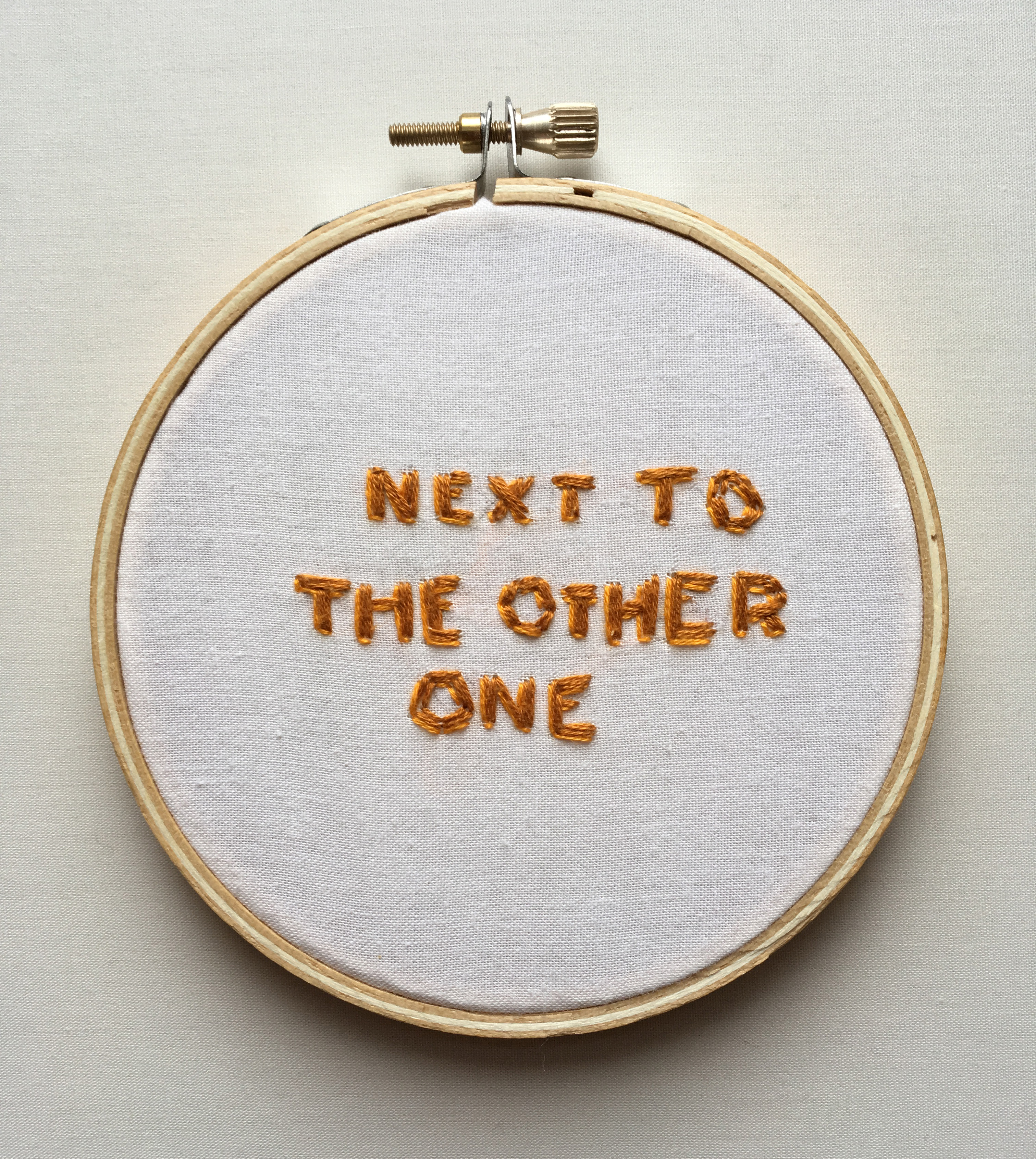 "An embroidery of the text ""next to the other one"" on white fabric stretched over a hoop."