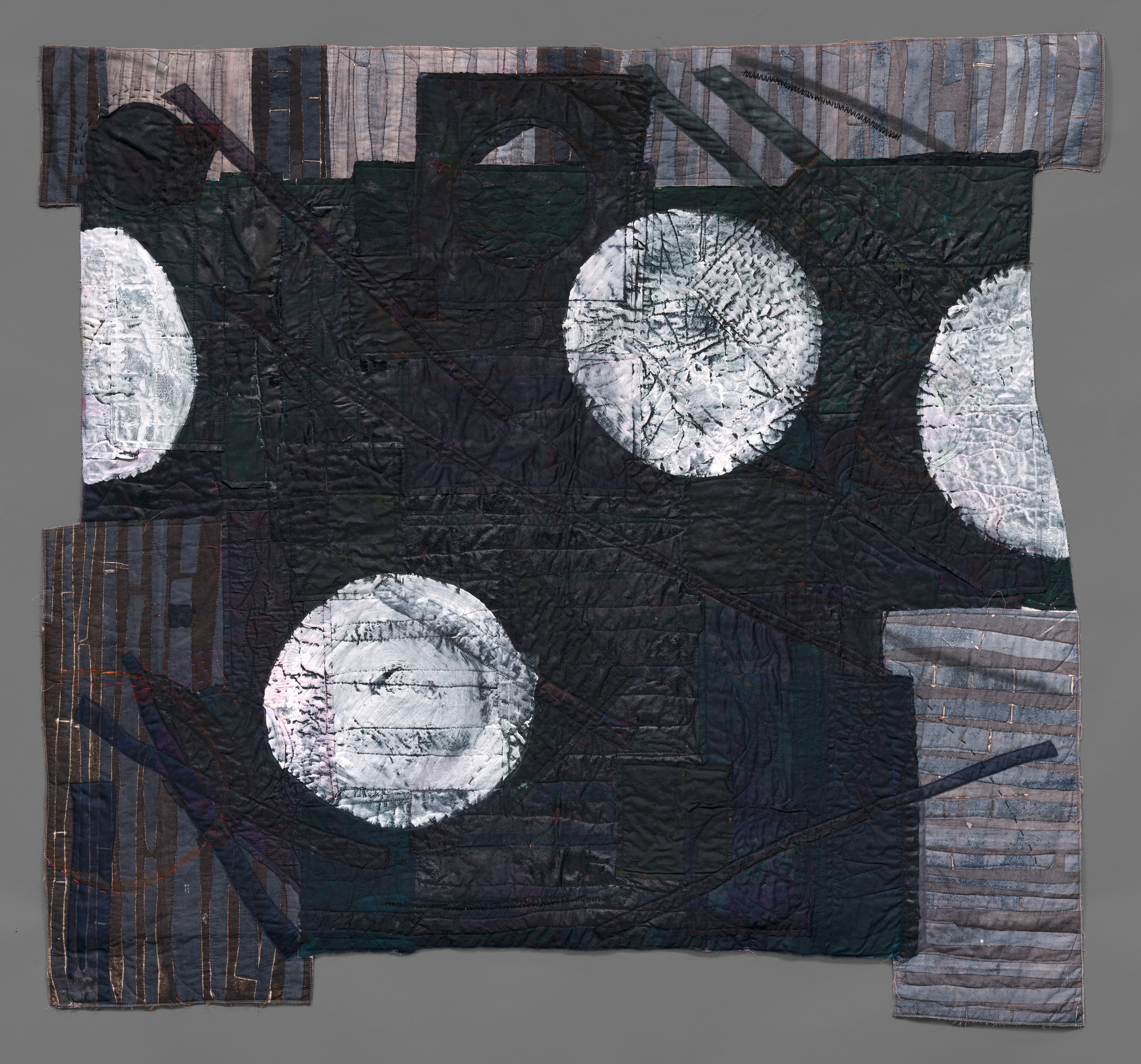 black-painted quilt with circles printed in white gesso
