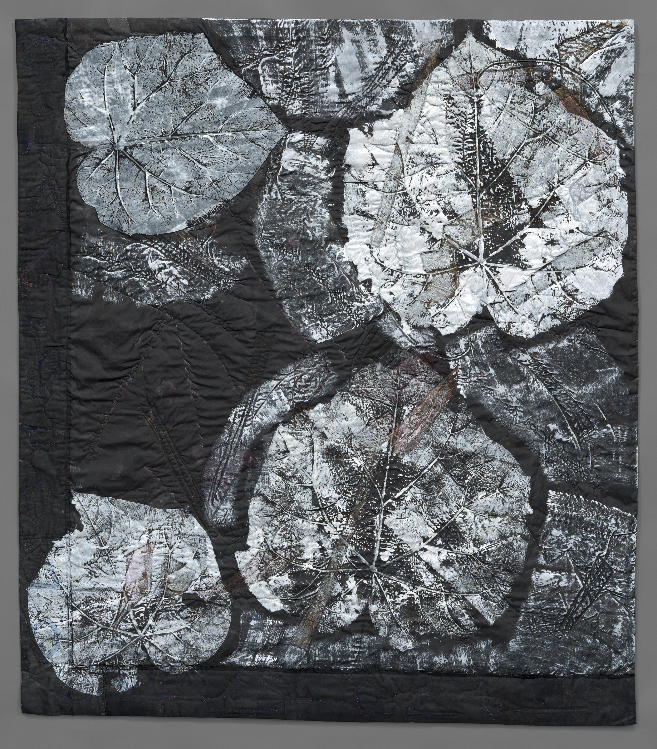 black-painted quilt with leaves printed in white gesso