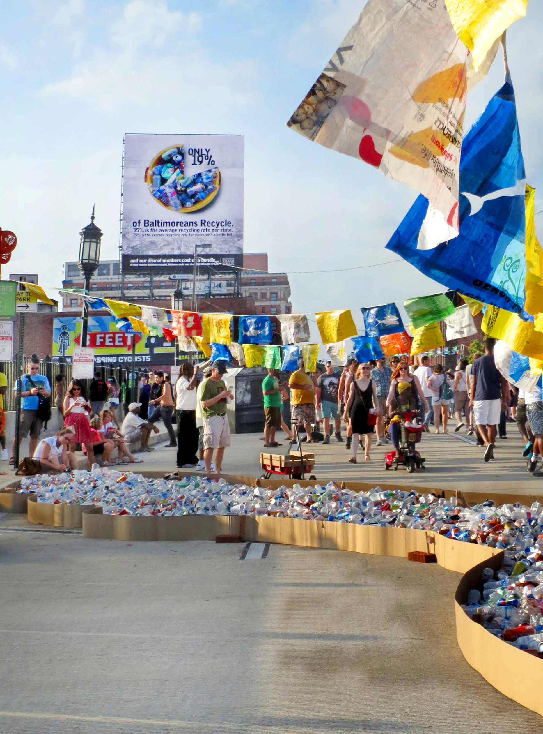 River of Recyclable items accompanied by 100 plastic bag flags with sea creatures cut in them.