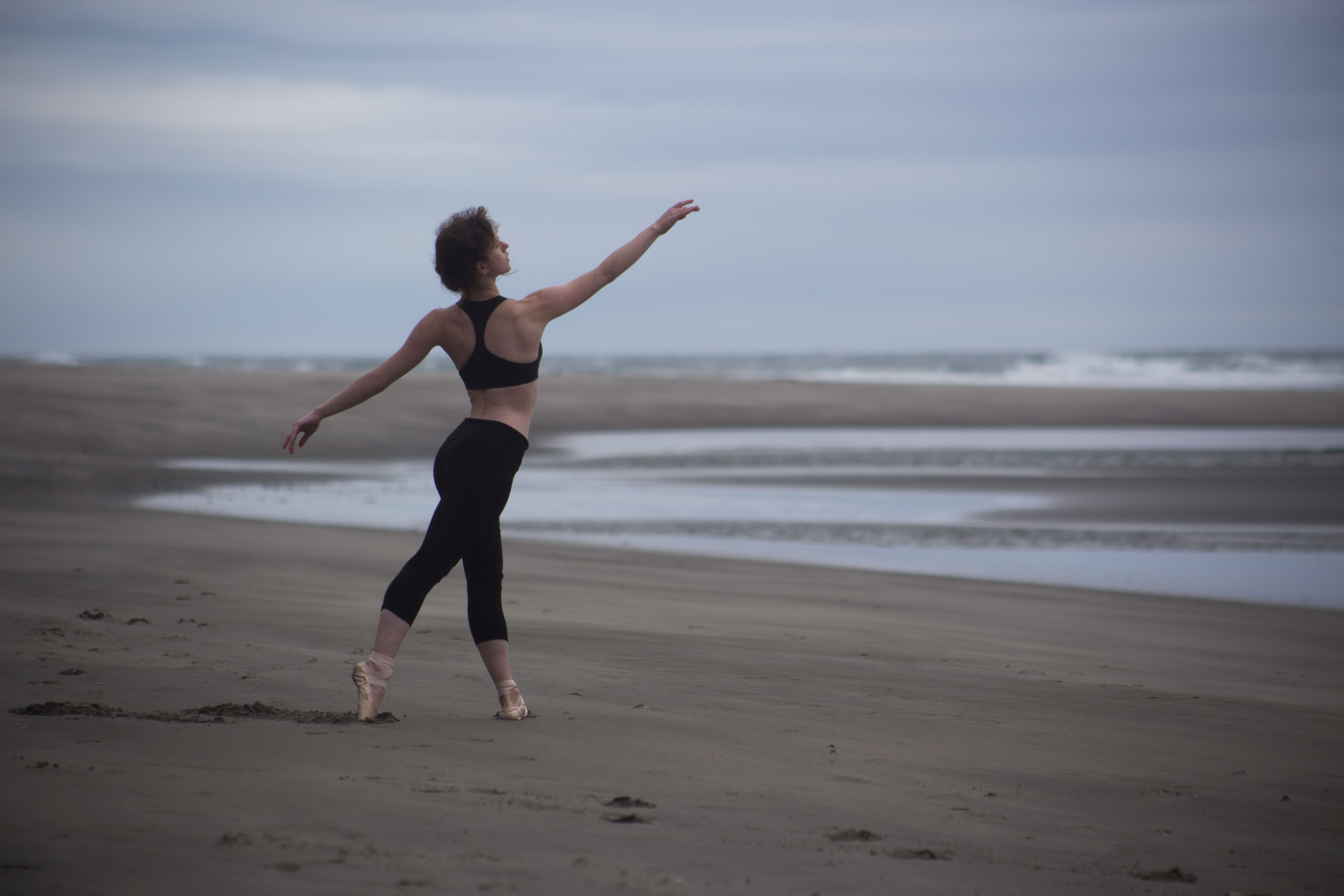 A ballet dance strikes a pose in the sand on Second Beach in Olympic National Park, Washington.