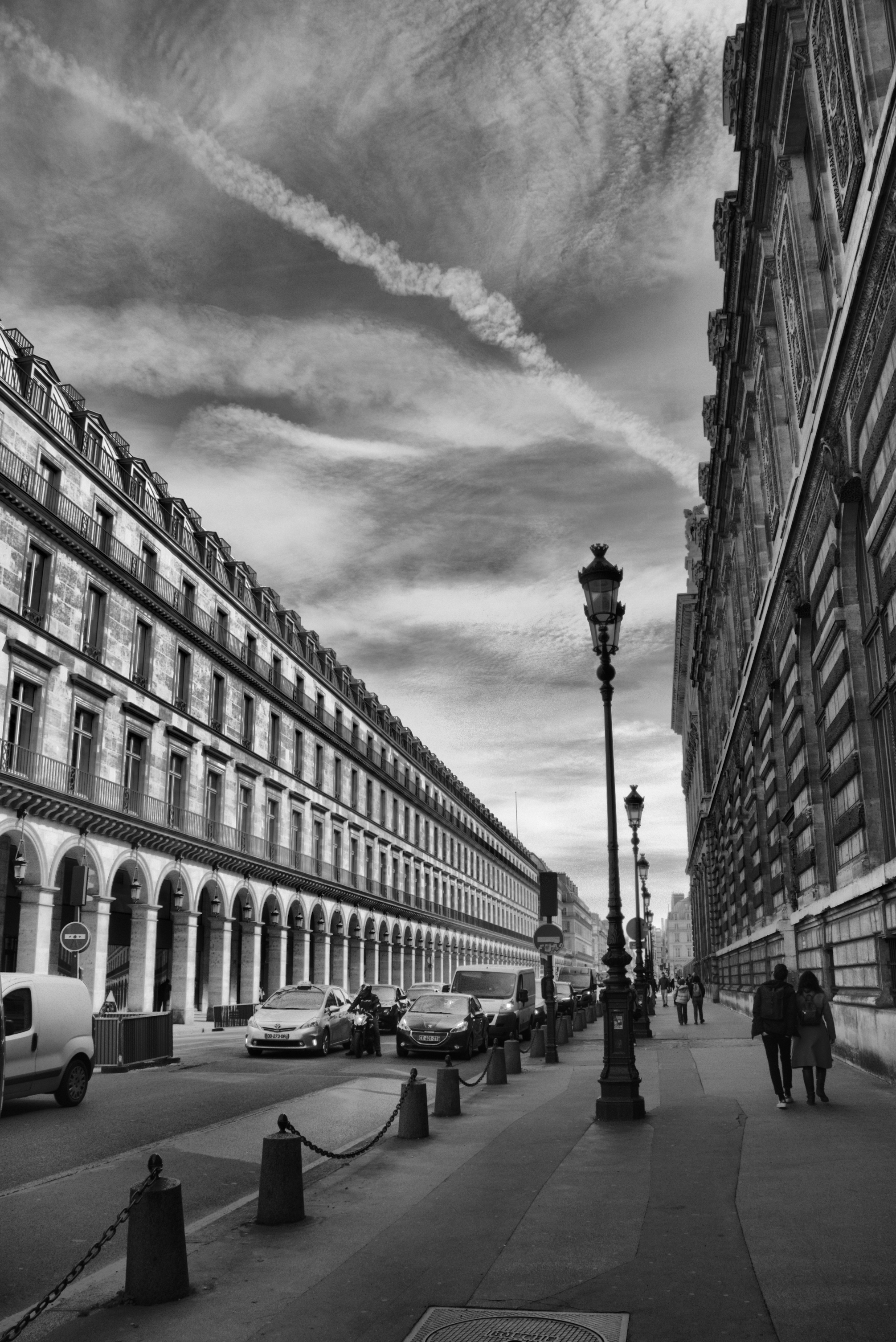 Black and white photo of a couple walking down the street in Paris.