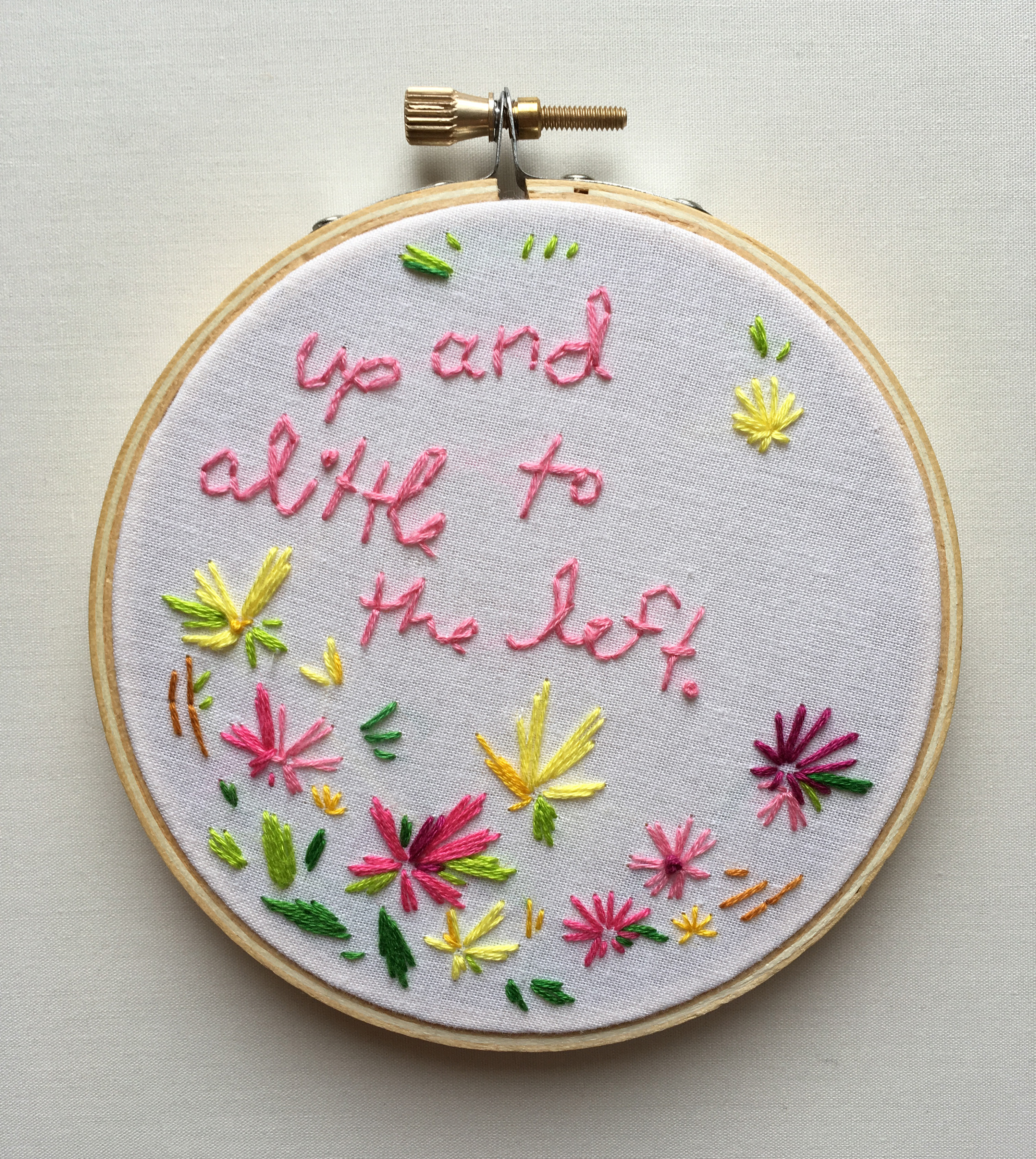"An embroidery of the text ""up and a little to the left"" on white fabric stretched over a hoop."