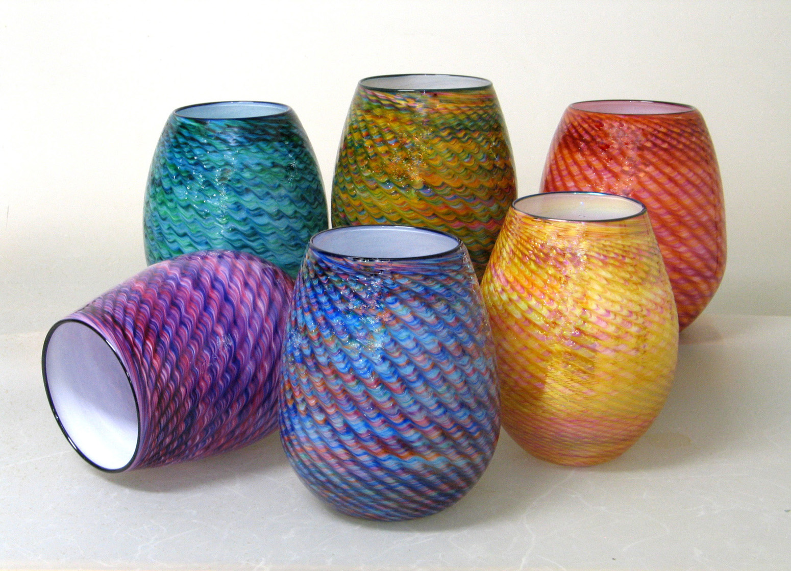 These glass Baskets are 'woven' using our own exclusive color mixes. The colors are spun into multi-chromatic threads and further textured using time honored free-hand techniques. Each basket receives a finishing accent of color in the form of a lip wrap. (10-11in. ht)