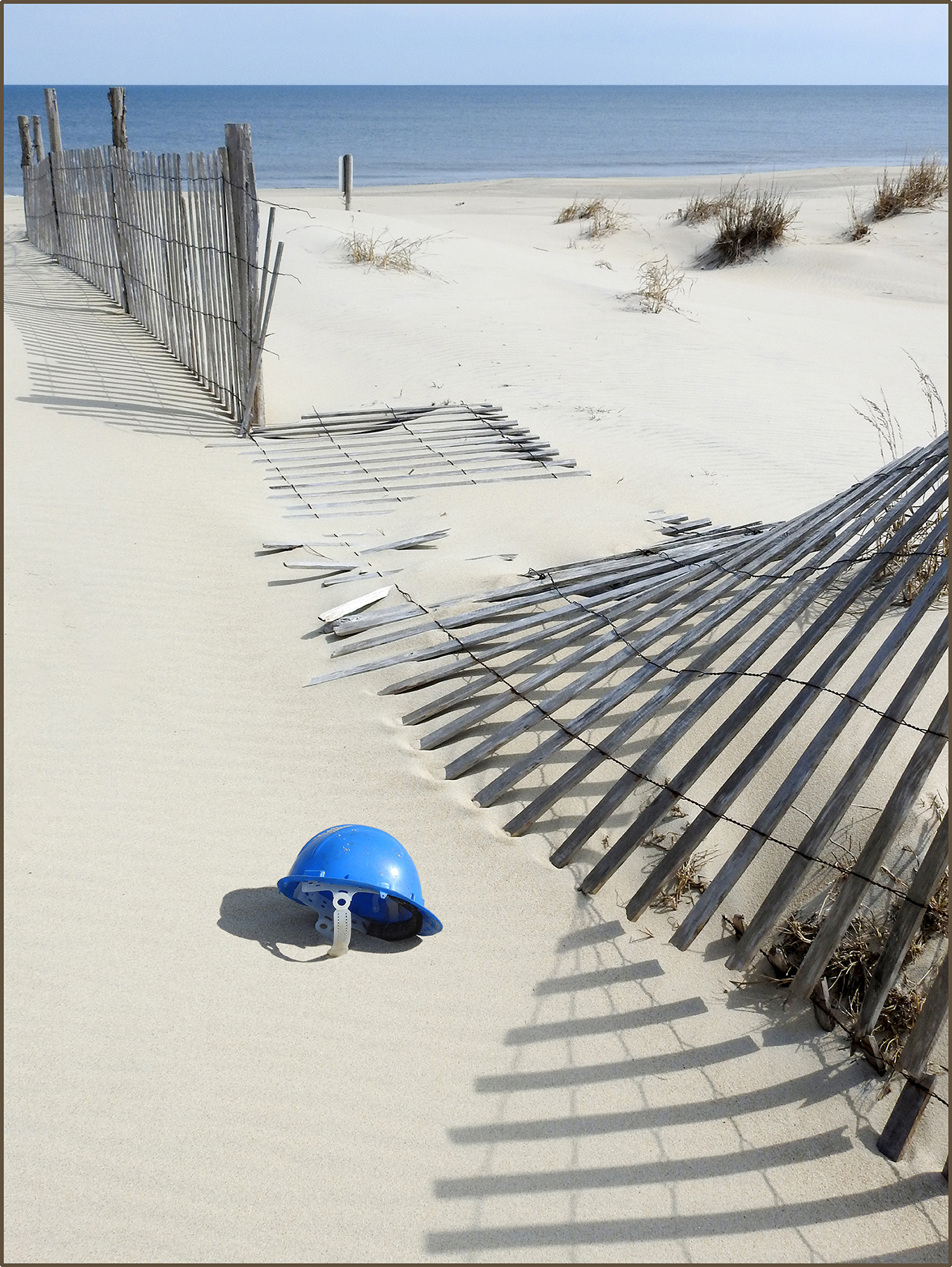 Lone blue helmet next to wind-blown beach fence on sunny Dewey Beach with Atlantic Ocean in background. Shadows cast by sun.