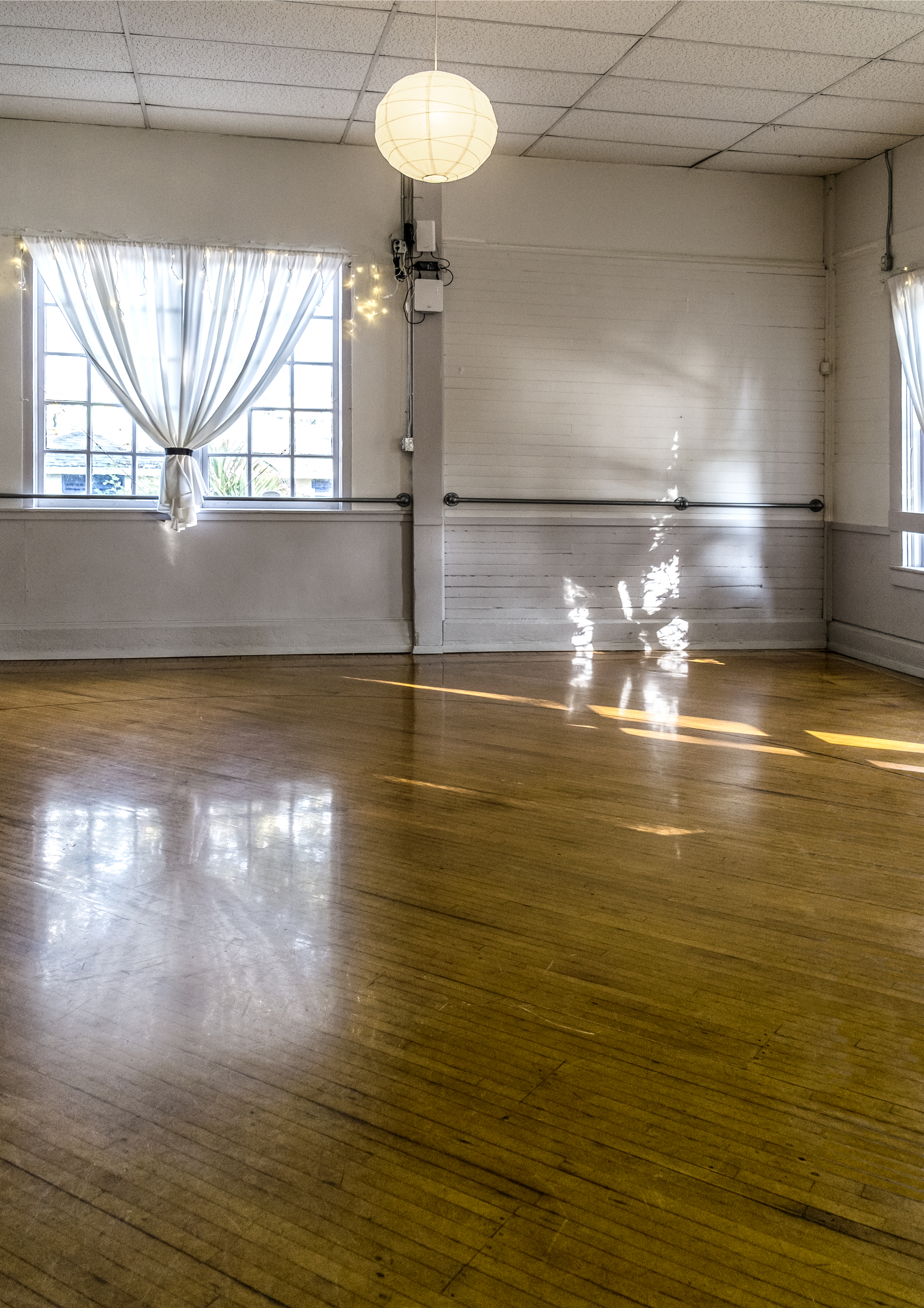 Windows from dance hall reflect light from outside onto polished wooden floor.
