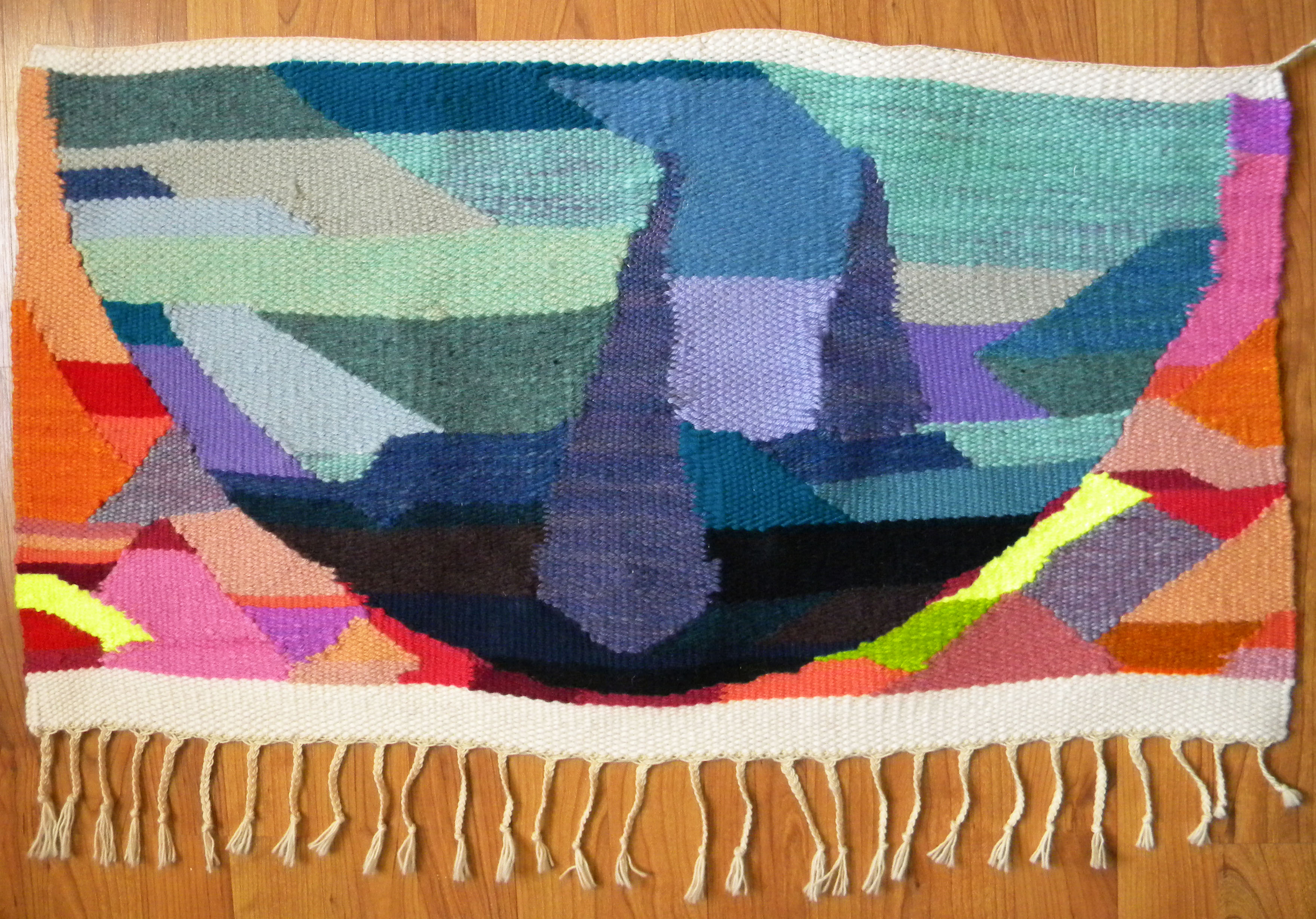 a colorful handwoven tapestry by Clare Nicholls