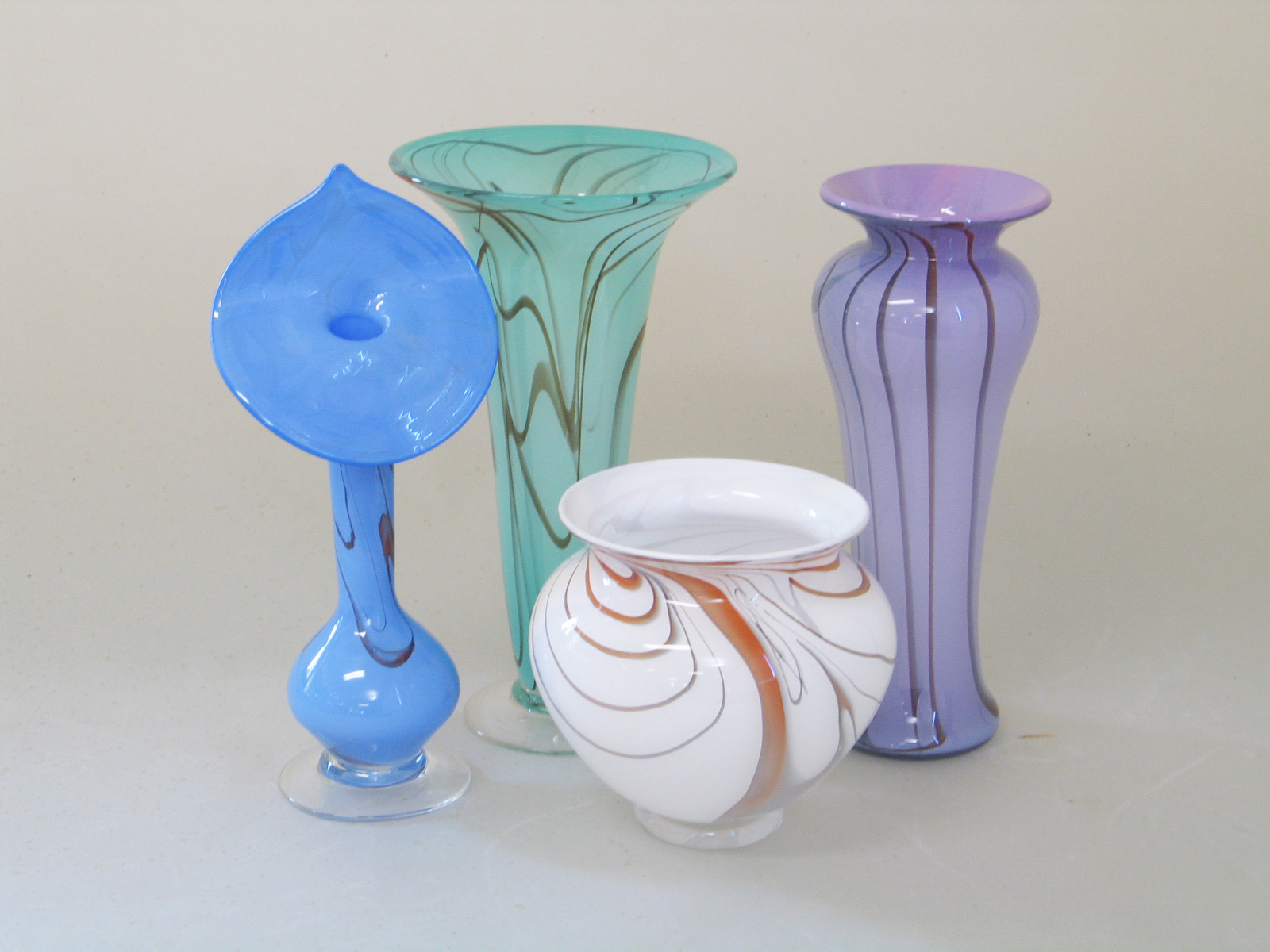 Opalescent blue, lavendar, white or jade and red glass are blended together to create the foundation for the various tones of color that flow throughout these individual works of art. Texture and color combine with form as the glass is hand shaped to its finished dimension. Each is a unique work, impossible to duplicate. Contact us with your request.