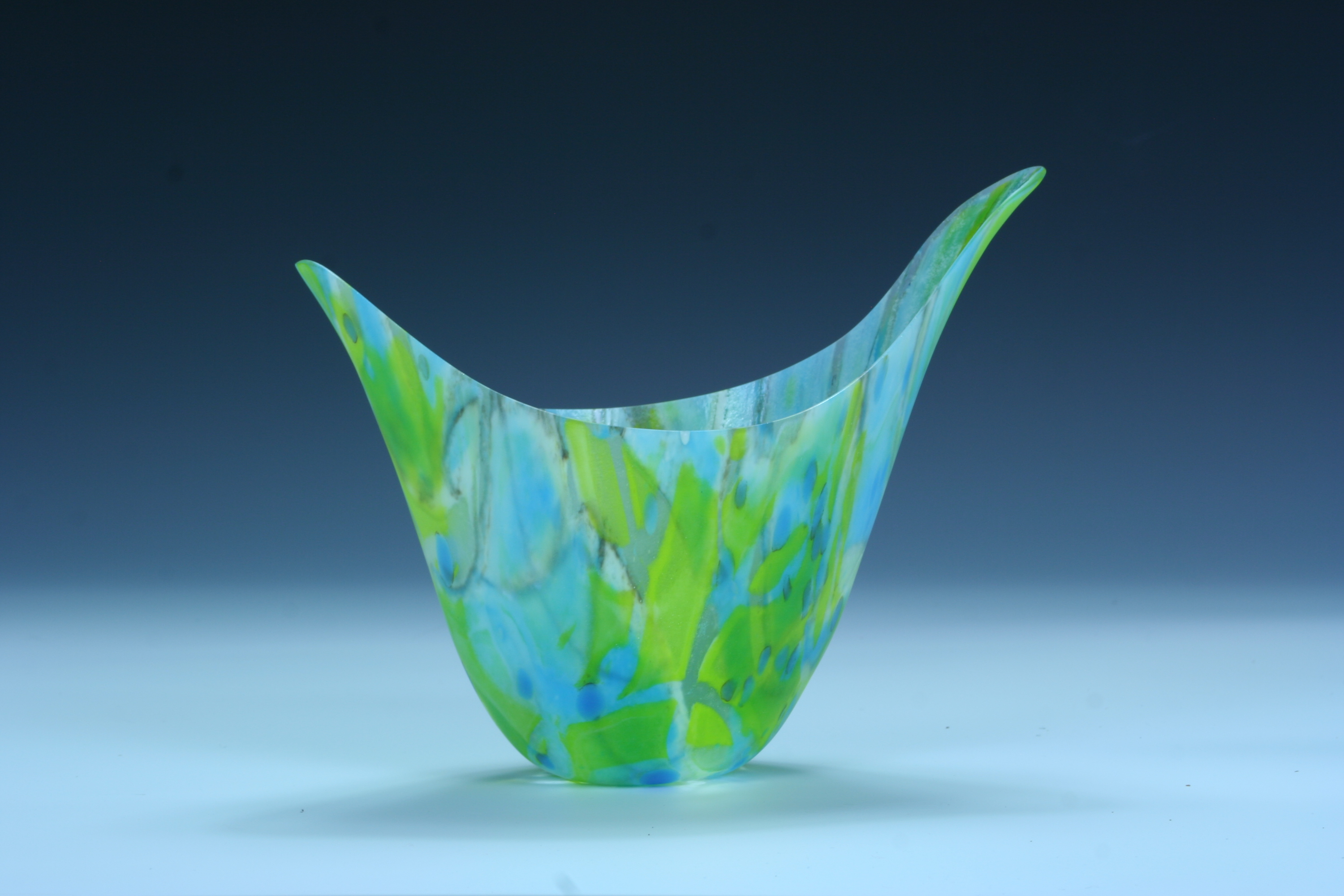 A kiln-formed vessel in blues and greens