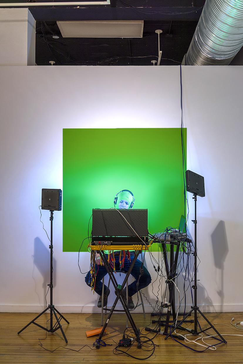 The picture depicts how the performance occurred before the green screen and the wire carries the sound and video over the wall