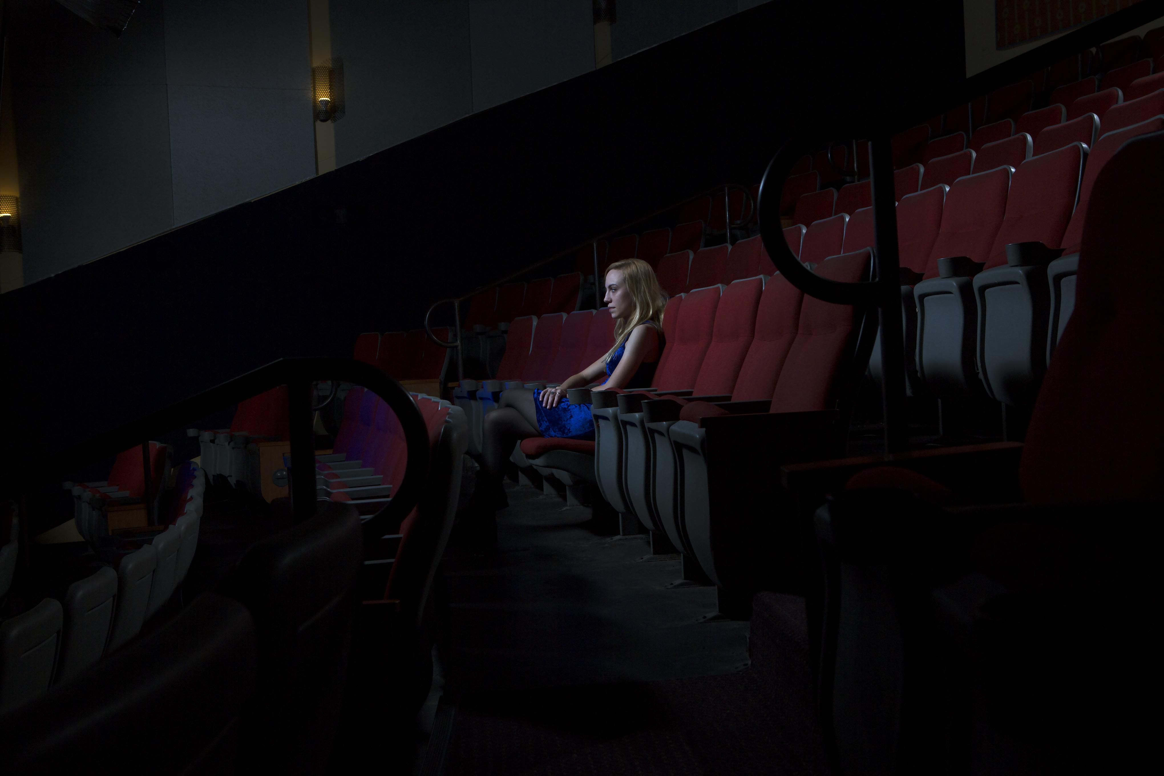 Woman sitting alone at movie theatre.