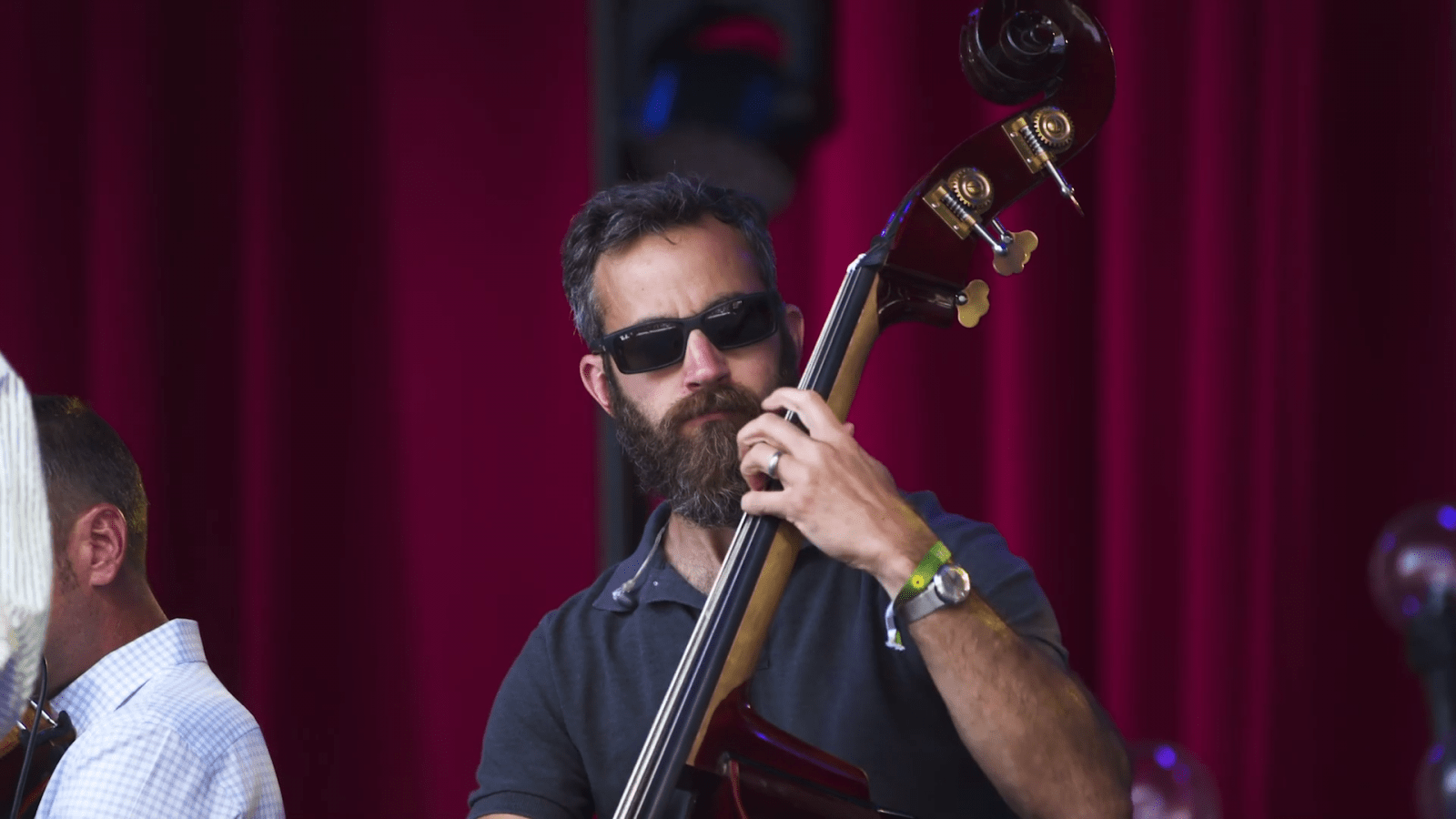 Man in sunglasses performs on an upright bass